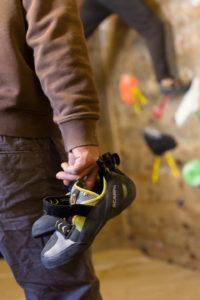 Boulderer mit seinen Schuhen in der Hand